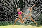 Teenage girls playing in sprinkler Stock Photo - Premium Royalty-Free, Artist: Siephoto, Code: 614-06625292