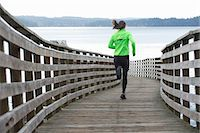 Woman running on wooden dock Stock Photo - Premium Royalty-Freenull, Code: 614-06625319