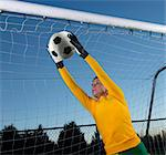 Soccer player catching ball in goal Stock Photo - Premium Royalty-Free, Artist: Blend Images, Code: 614-06625334