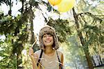 Woman carrying balloons in park Stock Photo - Premium Royalty-Free, Artist: Blend Images, Code: 614-06625361
