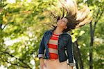 Woman tossing her hair in park Stock Photo - Premium Royalty-Free, Artist: Robert Harding Images, Code: 614-06625368