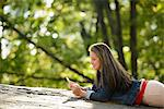 Woman using cell phone in park Stock Photo - Premium Royalty-Free, Artist: Blend Images, Code: 614-06625370