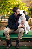 Man petting dog on park bench Stock Photo - Premium Royalty-Freenull, Code: 614-06625434