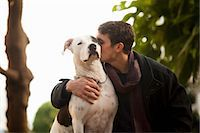 Man kissing dog outdoors Stock Photo - Premium Royalty-Freenull, Code: 614-06625436