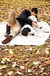 Man and dog relaxing on picnic blanket Stock Photo - Premium Royalty-Freenull, Code: 614-06625439