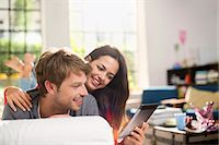 Couple using digital tablet on sofa Stock Photo - Premium Royalty-Freenull, Code: 6113-06625571