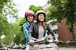 Couple riding scooter together on city street Stock Photo - Premium Royalty-Free, Artist: Cultura RM, Code: 6113-06625576