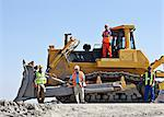 Workers on bulldozer smiling in quarry Stock Photo - Premium Royalty-Free, Artist: Westend61, Code: 6113-06625924