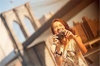 Woman taking picture by urban bridge Stock Photo - Premium Royalty-Freenull, Code: 6113-06626142