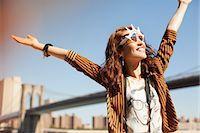 Woman in novelty sunglasses standing by urban bridge Stock Photo - Premium Royalty-Freenull, Code: 6113-06626160