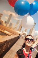 Woman with bunch of balloons on urban bridge Stock Photo - Premium Royalty-Freenull, Code: 6113-06626174