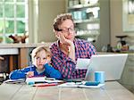 Bored father and son working at table Stock Photo - Premium Royalty-Free, Artist: CulturaRM, Code: 6113-06626332