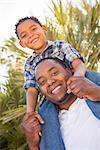 Happy Mixed Race Father and Son Playing Piggyback in the Park. Stock Photo - Royalty-Free, Artist: Feverpitched                  , Code: 400-06633881