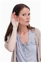 Close up of woman listening closely against a white background Stock Photo - Royalty-Freenull, Code: 400-06634524