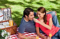 Woman putting food into her friends mouth as they lie on a blanket with a picnic basket,food and flowers Stock Photo - Royalty-Freenull, Code: 400-06635506