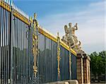 Palace of Versailles, France. The main entrance. Lattice fence with gold-plated details. Sculpture - allegory 