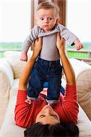 funny looking people - Woman Lying Down and Holding her Three Month Old Son Up in the Air Stock Photo - Premium Rights-Managednull, Code: 700-06645598