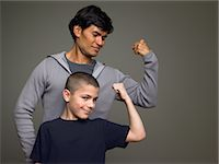 Father and son flexing muscles Stock Photo - Premium Royalty-Freenull, Code: 6114-06646128