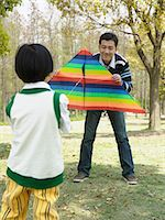 Father and son playing with a kite Stock Photo - Premium Royalty-Freenull, Code: 6114-06646196