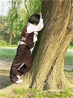 Boy playing hide and seek Stock Photo - Premium Royalty-Freenull, Code: 6114-06646207