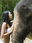Young woman stroking an elephant Stock Photo - Premium Royalty-Free, Artist: Westend61, Code: 6114-06646951
