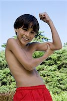 Boy flexing muscles Stock Photo - Premium Royalty-Freenull, Code: 6114-06647568