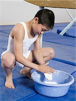 Gymnast putting chalk on his hands Stock Photo - Premium Royalty-Freenull, Code: 6114-06647679