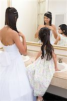 Girl watching sister prepare for quinceanera Stock Photo - Premium Royalty-Freenull, Code: 6114-06648187