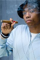 Young man having a cigar Stock Photo - Premium Royalty-Freenull, Code: 6114-06648400