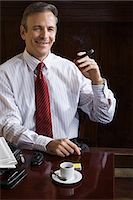 Businessman with cigar Stock Photo - Premium Royalty-Freenull, Code: 6114-06649146