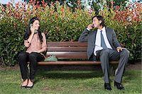 flirting - Couple using different phones on bench Stock Photo - Premium Royalty-Freenull, Code: 6114-06650013