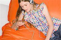 A teenage girl listening to music Stock Photo - Premium Royalty-Freenull, Code: 6114-06651120