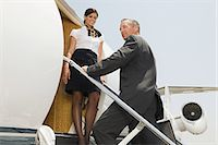 Stewardess and businessman boarding jet Stock Photo - Premium Royalty-Freenull, Code: 6114-06652213