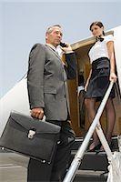 Stewardess and businessman boarding jet Stock Photo - Premium Royalty-Freenull, Code: 6114-06652227