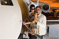 Glamorous couple boarding jet Stock Photo - Premium Royalty-Freenull, Code: 6114-06652241