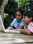 Father and son with laptop in garden Stock Photo - Premium Royalty-Free, Artist: Robert Harding Images, Code: 6114-06652355