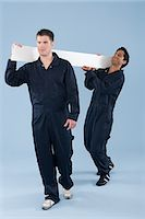 Two labourers carrying a plank Stock Photo - Premium Royalty-Freenull, Code: 6114-06652907