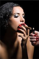 Woman lighting a cigar Stock Photo - Premium Royalty-Freenull, Code: 6114-06653602