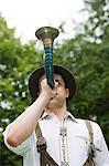 A german man in national dress playing the horn Stock Photo - Premium Royalty-Free, Artist: Blend Images, Code: 6114-06653861