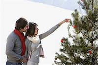 snow christmas tree white - Couple decorating a christmas tree Stock Photo - Premium Royalty-Freenull, Code: 6114-06654866