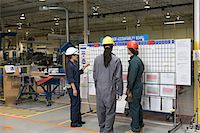 Three factory workers standing near message board Stock Photo - Premium Royalty-Freenull, Code: 6114-06655644