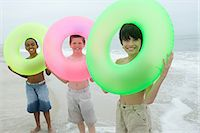 Three boys holding inflatable rings Stock Photo - Premium Royalty-Freenull, Code: 6114-06657141