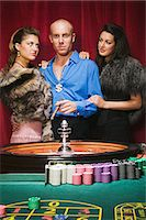 Women with wealthy man at roulette table Stock Photo - Premium Royalty-Freenull, Code: 6114-06658575