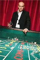 Wealthy man at a craps table Stock Photo - Premium Royalty-Freenull, Code: 6114-06658580