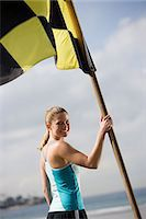 Woman holding beach flag Stock Photo - Premium Royalty-Freenull, Code: 6114-06658738