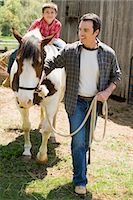 Father assisting son horseback riding Stock Photo - Premium Royalty-Freenull, Code: 6114-06659546