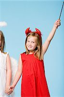 Twin girls dressed as an angel and devil Stock Photo - Premium Royalty-Freenull, Code: 6114-06659751