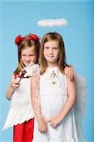 Twin girls dressed as an angel and devil Stock Photo - Premium Royalty-Freenull, Code: 6114-06659755