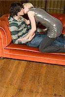 Teenagers kissing on a sofa Stock Photo - Premi