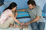 Couple playing checkers Stock Photo - Premium Royalty-Free, Artist: Westend61                , Code: 6114-06661311